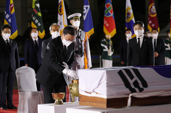 President Moon Jae-in pays respects to the remains of Hong Beom-do, a heroic Korean independence fighter repatriated from Kazakhstan 78 years after his death, at Seoul Air Base in Seongnam, Gyeonggi, in a late-night ceremony Sunday, coinciding with Liberation Day. [YONHAP]