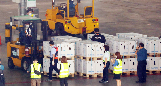 Workers unload boxes carrying 1.6 million doses of Pfizer's Covid-19 vaccine, which the government has secured under a direct contract with the pharmaceutical giant, from a chartered plane at Incheon International Airport on Wednesday. [NEWS1]