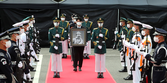The remains of Hong Beom-do, a revered Korean independence fighter who died in Kazakhstan 78 years ago, arrive in a flag-draped casket for his burial ceremony attended by President Moon Jae-in, First Lady Kim Jung-sook, party leaders, ministers, diplomats and other dignitaries Wednesday morning at the Daejeon National Cemetery. [YONHAP]