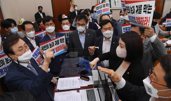 Opposition People Power Party lawmakers attempt to block the approval of an amendment to the Press Arbitration Act by Culture Committee Chairman Do Jong-hwan on Thursday. [YONHAP]