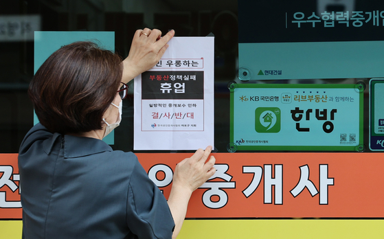 An employee of a real estate agency in Seoul on Thursday puts up a sign saying the agency will temporarily close in protest of the government's attempt to lower real estate commissions. The Ministry of Land, Infrastructure and Transport is mulling ways to cut real estate commissions. [YONHAP]