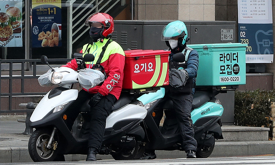 Baedal Minjok and Yogiyo riders deliver food in Jongno District, central Seoul on Dec. 29. [NEWS1]