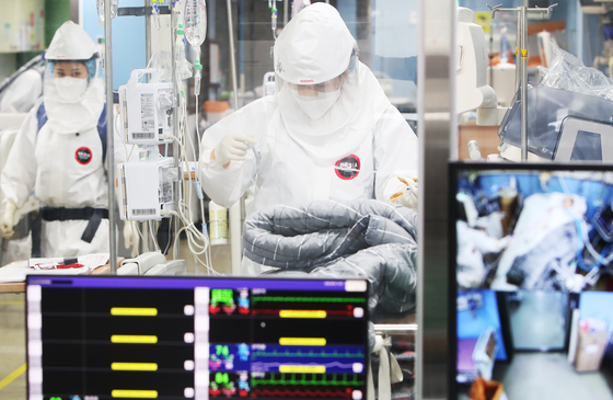 Medical staff at Bagae Hospital, a Covid-19 designated hospital in Pyeongtaek, Gyeonggi, treat Covid-19 patients while in their protective gear on Thursday. [YONHAP]