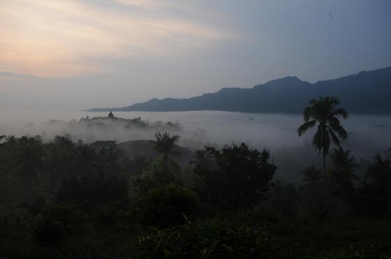 Borobudur Temple Compounds during a sunrise on a misty day [BOROBUDUR PARK MANAGEMENT]