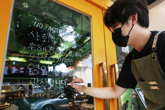 An employee at a coffee shop in Seoul writes a notice on Sunday explaining new social distancing rules to take effect the following day, which would limit business hours of restaurants and cafes in areas under Level 4 to 9 p.m. from the current 10 p.m. [NEWS1]
