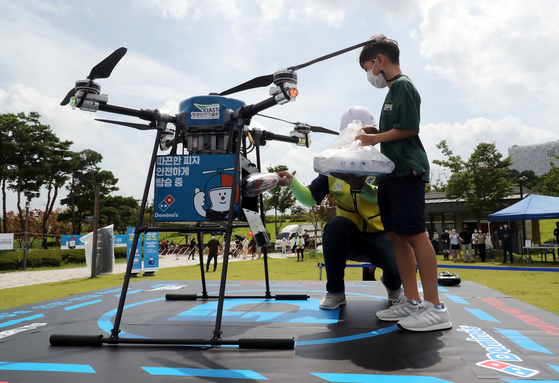 A boy receives a pizza delivered by a drone at Sejong Lake Park in Sejong City on Sunday. It was the first demonstration of a commercial drone delivery in collaboration with the drone start-up P-square and Domino's Pizza. The Transportation Ministry said it could expand the zone for drone delivery after evaluating the pilot project through the end of October.  [NEWS1]