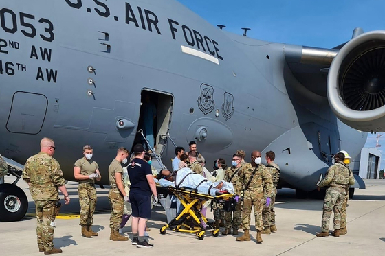 An Afghan mother who gave birth aboard a U.S. Air Force C-17 aircraft during an evacuation flight is transported to a nearby medical facility after landing at Ramstein Air Base in Germany Saturday. [U.S. AIR FORCE]