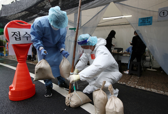 Medical workers deploy sand bags at tents for Covid-19 testing in Gwangju on Monday as winds picked up as Typhoon Omais approached the Korean Peninsula. [YONHAP]