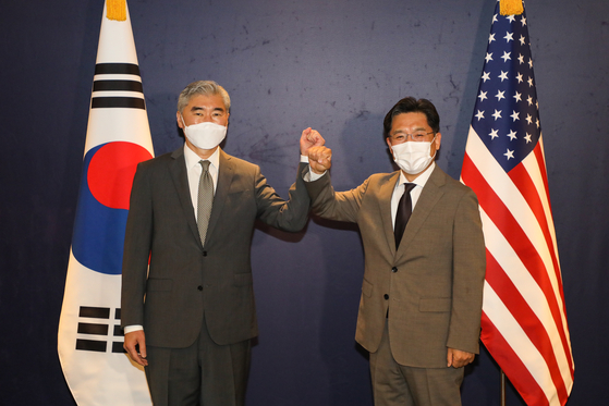 South Korea's top nuclear envoy, Noh Kyu-duk, right, and his U.S. counterpart, Sung Kim, bump their fists ahead of a meeting at The Plaza Hotel in central Seoul Monday morning to discuss efforts to get North Korea to return to the dialogue table, including humanitarian cooperation. [JOINT PRESS CORPS]