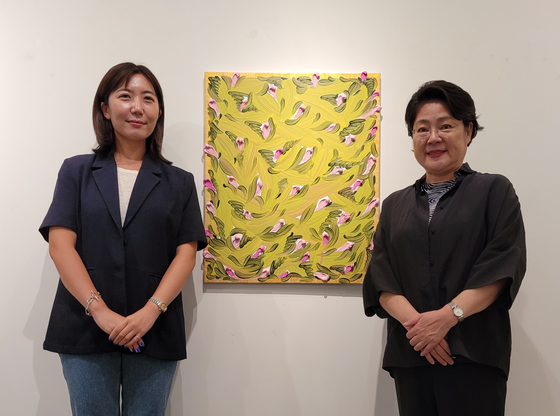 Lee Hwaik, right, founder and head of Lee Hwaik Gallery, and artist Kim Mee-young, who will participate in the second part of the gallery's special exhibition to celebrate the 20th anniversary pose with Kim's painting at the gallery in central Seoul on Aug. 18. [MOON SO-YOUNG]