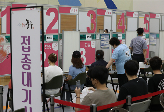 People wait for inoculations at a Covid-19 vaccination center in Jung District, central Seoul, on Tuesday afternoon. As of Monday midnight, 51.2 percent of the country's population had received one vaccine shot. [NEWS1]