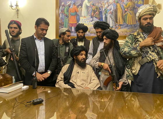 Taliban fighters take control of the presidential palace in Kabul Sunday after Afghan President Ashraf Ghani fled the country. [AP/YONHAP]
