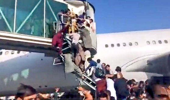 Mayhem at the airport in Kabul on Sunday as people try to evacuate out of the country after the Taliban forces swept into the Afghan capital. [SCREEN CAPTURE FROM A TWITTER ACCOUNT]