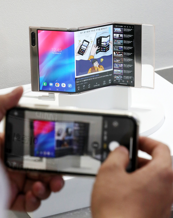 """A visitor takes a photo of Samsung Display's """"Flex In and Out"""" at the International Meeting on Information Display (IMID) 2021 in Coex, southern Seoul, on Wednesday. The Flex In and Out is a display panel that can be folded twice. [NEWS1]"""