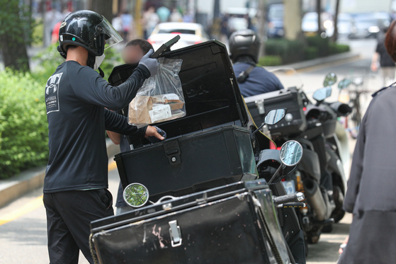 A delivery worker makes a delivery in Jongno District, central Seoul, on July 12. [NEWS1]
