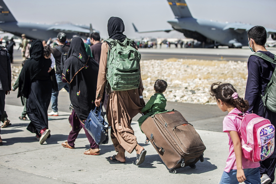 Afghan families await a flight out at Hamid Karzai International Airport in Afghanistan Tuesday. [AP/YONHAP]