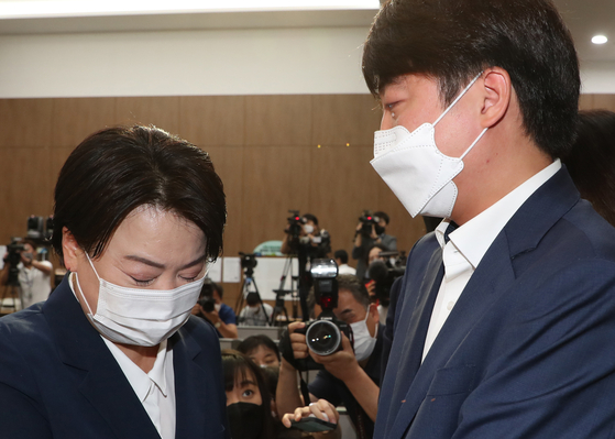 People Power Party Rep. Yun Hee-suk, left, and party Chairman Lee Jun-seok shed tears on Wednesday as Lee tries to dissuade Yun from giving up her lawmaker post. [YONHAP]