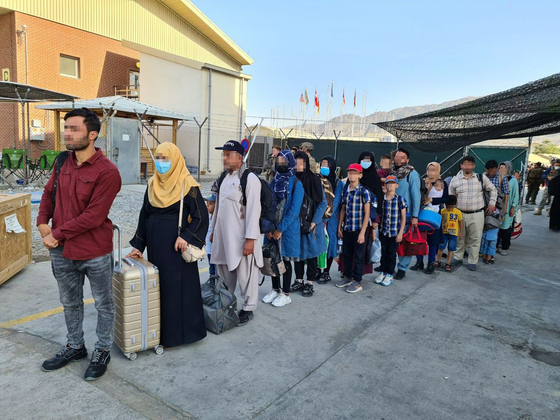 Afghans who have worked for the Korean government and their family members wait in line to board a South Korean Air Force transport plane at the Kabul airport Tuesday, local time. Some 390 evacuees are set to arrive at Incheon International Airport Thursday. [FOREIGN MINISTRY]