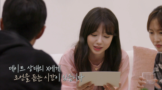 A scene from ″Transit Love″ shows a cast member reading advice from her love interest's ex. [SCREEN CAPTURE]