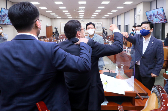 From left: Democratic Party lawmakers Kim Nam-kuk, Park Ju-min, Kim Seung-won and Kim Young-bae congratulate each other in the early hours of Wednesday after approving a controversial media bill at a Judiciary and Legislation Committee meeting at the National Assembly presided over by Park. [KIM KYUNG-ROK]