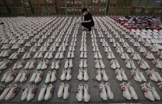 A customs officer examines fake luxury sneakers at the Busan Regional Customs office on Thursday. The customs office announced Thursday it caught three people who smuggled some 2,000 fake Nike, Gucci and Balenciaga sneakers worth 1.7 billion won ($1.5 million) into Korea. [SONG BONG-GEUN]