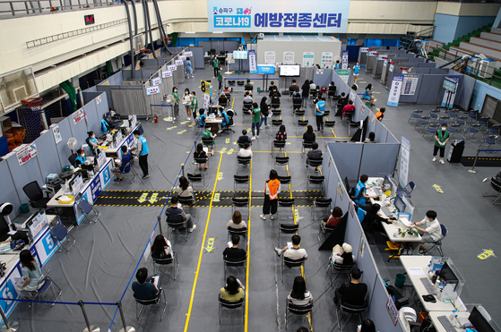 On the second day of Covid-19 vaccinations for people between the ages of 18 and 49 on Friday, people await shots at a vaccination center at the Songpa District's Sports and Culture Center in Seoul.  [YONHAP]