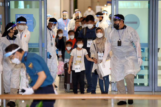 Afghan evacuees arrive at Incheon International Airport on Friday. After a first group of 377 arrived on Thursday, the Korean military completed its evacuation operation on Friday by bringing in a second group of 13 .  [YONHAP]