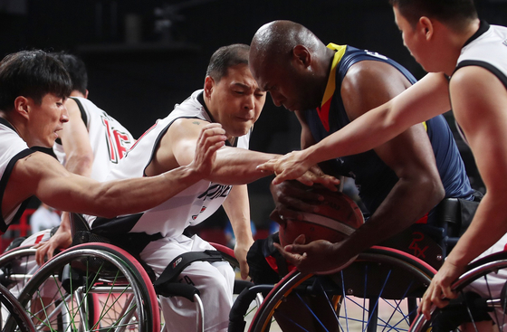 Korean wheelchair basketball players fight for the ball during a game against Colombia at the 2020 Tokyo Paralympics on Saturday. [NEWS1]