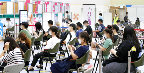 People wait to get a Covid-19 vaccine at a vaccination center in Jung District, central Seoul, on Monday afternoon. As of the previous day, 55.8 percent of the population have received their first shots of Covid-19 vaccines, with 28.5 percent being fully vaccinated. [NEWS1]