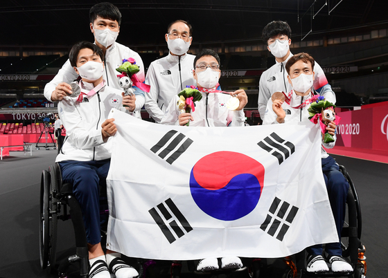 Joo Young-dae, center, won Korea's first gold medal of the Tokyo Paralympics on Monday, beating teammate Kim Hyeon-uk, left, in the men's table tennis class one gold medal match. Kim took silver and Nam Ki-won, also of Korea, took one of two bronze medals. [NEWS1]