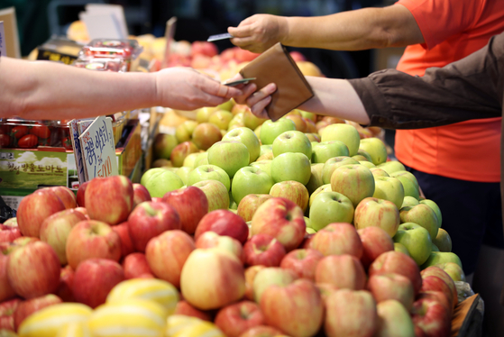 Shoppers buy fruit at a traditional market in downtown Seoul on Monday. The government said it will increase the volume of its agricultural food supply by 2.4 times, including cabbages, radishes, apples and pears, ahead of the Chuseok harvest holiday which falls on Sept. 21. [YONHAP]