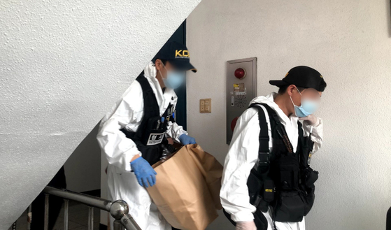 Police forensic investigators on Sunday leave the residence of a murder suspect who turned himself in and confessed to killing of two women. A body of a woman was found inside his home in Songpa District, southern Seoul, and the other in a car he drove to the police precinct to surrender himself Sunday morning. [NEWS1]
