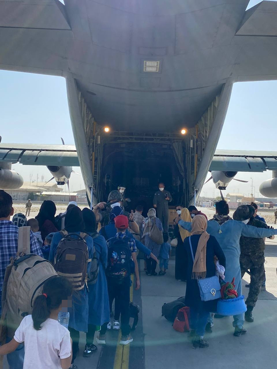 Afghans bound for Korea board a Korean Air Force transport plane at the Kabul airport Tuesday, local time. The Korean government flew three military aircraft to Pakistan earlier this week to airlift 390 Afghan evacuees, including 100 children. [FOREIGN MINISTRY]