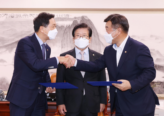 Democratic Party floor leader Yun Ho-jung, right, shakes hands on Tuesday at the National Assembly with his People Power Party counterpart Kim Gi-hyeon, left, after the two parties reached an agreement to create a consultative body to review a controversial media bill at a meeting convened by Speaker Park Byeong-seug. [LIM HYUN-DONG]