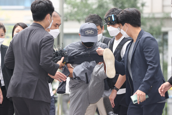 A murder suspect on Tuesday kicks reporters on his way to a warrant hearing at the Seoul Eastern District Court. [YONHAP]
