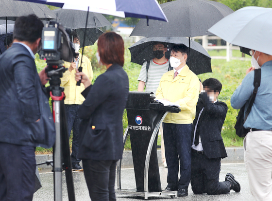 A Justice Ministry official kneels down to hold an umbrella for Vice Justice Minister Kang Sung-kook during his speech on a rainy day earlier this week.  [YONHAP]