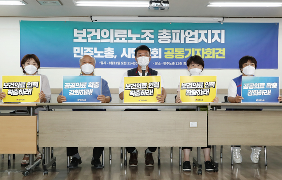 Members of the Korean Confederation of Trade Unions, associated with the Korean Health and Medical Workers' Union, hold a press conference in Seoul on Tuesday to support the union's planned walkout on Sept. 2. The union of medical workers will launch a strike to call for the government to expand public medical services and increase the number of medical workers. [YONHAP]