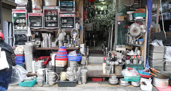 Kitchenware is stacked outside a secondhand store in Hwanghak-dong in Jongro, central Seoul on Wednesday. Used dishes and bowls have become a common site at secondhand stores as restaurants shutdown during the Covid-19 pandemic. According to a Korea Economic Research Institute survey of 500 business between Aug. 10 and 25, 39.4 percent said they are considering shutting down their business. [YONHAP]
