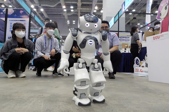 A team of engineers demonstrate their robot at the AI Korea 2021 exhibition in Haeundae, Busan, on Wednesday. The exhibition showcases artificial intelligence and blockchain technology from various companies, and runs through Friday. [YONHAP]