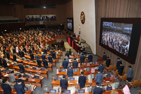 Lawmakers stand during the opening of the National Assembly's 391st regular session on Wednesday in Yeouido, southern Seoul. This is the last regular parliamentary session before President Moon Jae-in's term ends in March 2022. [NEWS1]