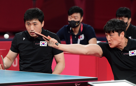 Korea's Kim Young-gun, left, and Kim Jung-gil take on China's Cao Ningning and Guo Xingyuan in the men's team class four to five gold medal match on Thursday. [NEWS1]