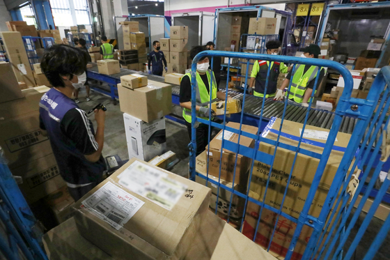 Delivery workers sort packages at a warehouse in Songpa District, southern Seoul, on Sept. 3. [NEWS1]