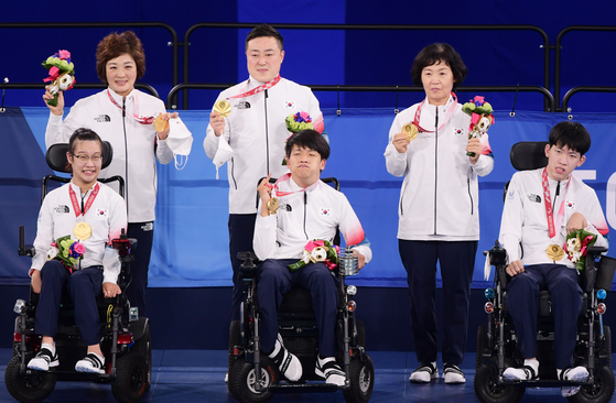 From left, Choi Ye-jin, Jeong Ho-won and Kim Han-soo celebrate their mixed boccia pairs sport class three gold medals on the 2020 Tokyo Paralympics podium at Ariake Arena in Tokyo on Saturday. [NEWS1]