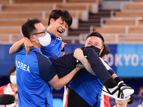 Jeong Ho-won, center, celebrates with his sport assistant and coach after winning the mixed pair boccia sport class three gold medal on Saturday at the Ariake Arena in Tokyo. [JOINT PRESS CORPS]