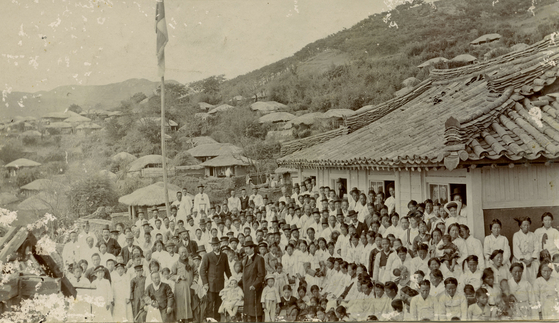 Australian missionaries, James Mackenzie and Andrew Adamson, standing with Koreans in front of Tongyeong Mission which is still in place, in this photo dated 1901. [KYONGGI UNIVERSITY SOSUNG MUSEUM]