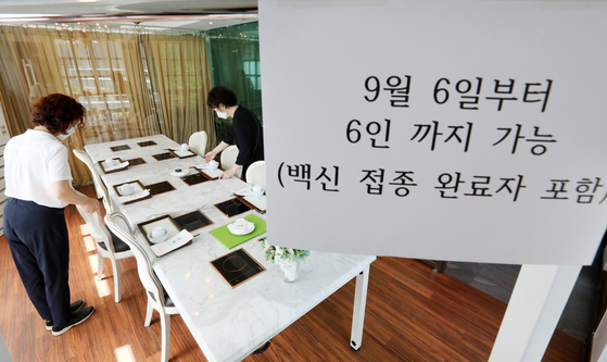 A sign describing the soon-to-be-eased social distancing rules is put up in a restaurant in Seoul on Sunday. Closing hours of restaurants and cafes will be extended by one hour to 10:00 p.m. starting Sept. 6, with gatherings of up to six people including fully vaccinated people to be allowed. [NEWS1]
