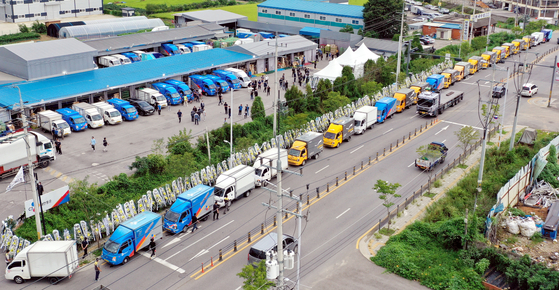 Dozens of delivery trucks line the streets next to a logistics terminal in Gimpo, Gyeonggi, on Thursday, in remembrance of the late logistics agency manager, Lee. Leaving behind a two-page suicide note detailing harassment by his deliverymen in the Parcel Delivery Workers' Solidarity Union, Lee committed suicide on Aug. 30. [YONHAP]