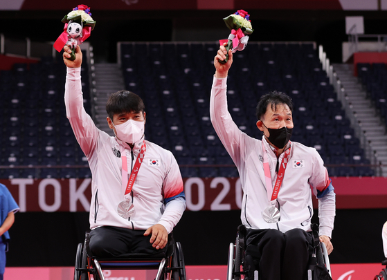 Kim Jung-jun and Lee Dong-seop pose after winning silver in the men's doubles WH badminton tournament at the 2020 Paralympics in Tokyo on Sunday. [YONHAP]