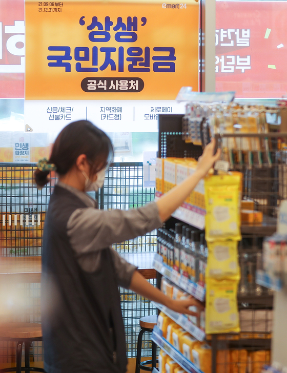 A sign posted at a convenience store in Seoul on Sunday notifies customers that it is accepting emergency relief grant payments until the end of this year. The government's 250,000 won ($210) emergency relief grant application starts Monday. [YONHAP]