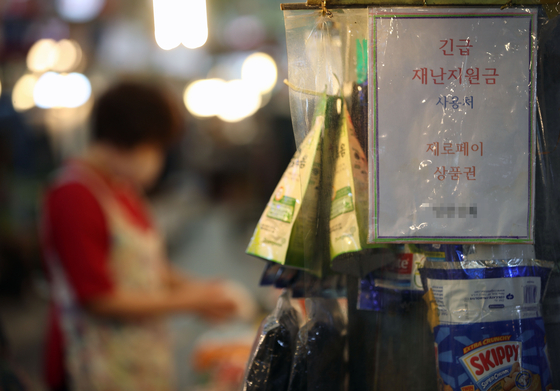 A store in a traditional market in Seoul on Monday posts a notice informing customers that it will accept payment in emergency relief grants from the government. [YONHAP]